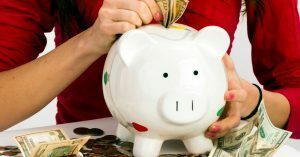 Woman putting money into savings piggy bank